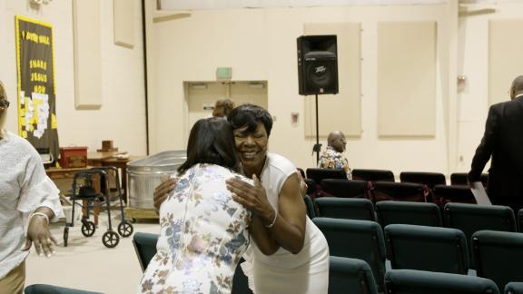 Jameria Moore hugs a woman in Hopewell Baptist Church in Birmingham, Alabama on Sunday, June 3.