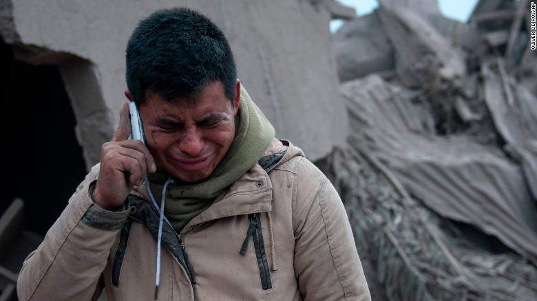 Boris Rodriguez, 24, who is searching for his wife, cries after seeing the condition of his neighborhood, destroyed by the erupting Volcan de Fuego.