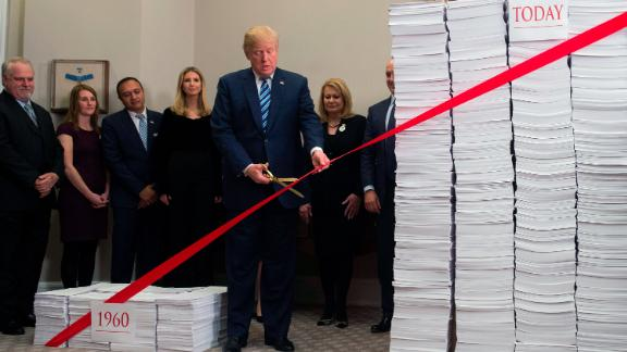 US President Donald Trump uses gold scissors to cut a red tape tied between two stacks of papers representing the government regulations of the 1960s (L) and the regulations of today (R) after he spoke about his administration's efforts in deregulation in the Roosevelt Room of the White House in Washington, DC on December 14, 2017. / AFP PHOTO / SAUL LOEB        (Photo credit should read SAUL LOEB/AFP/Getty Images)