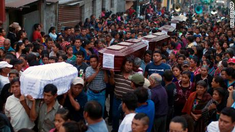 People carry the coffins of  victims of the volcanic eruption in a procession Monday in Alotenango.