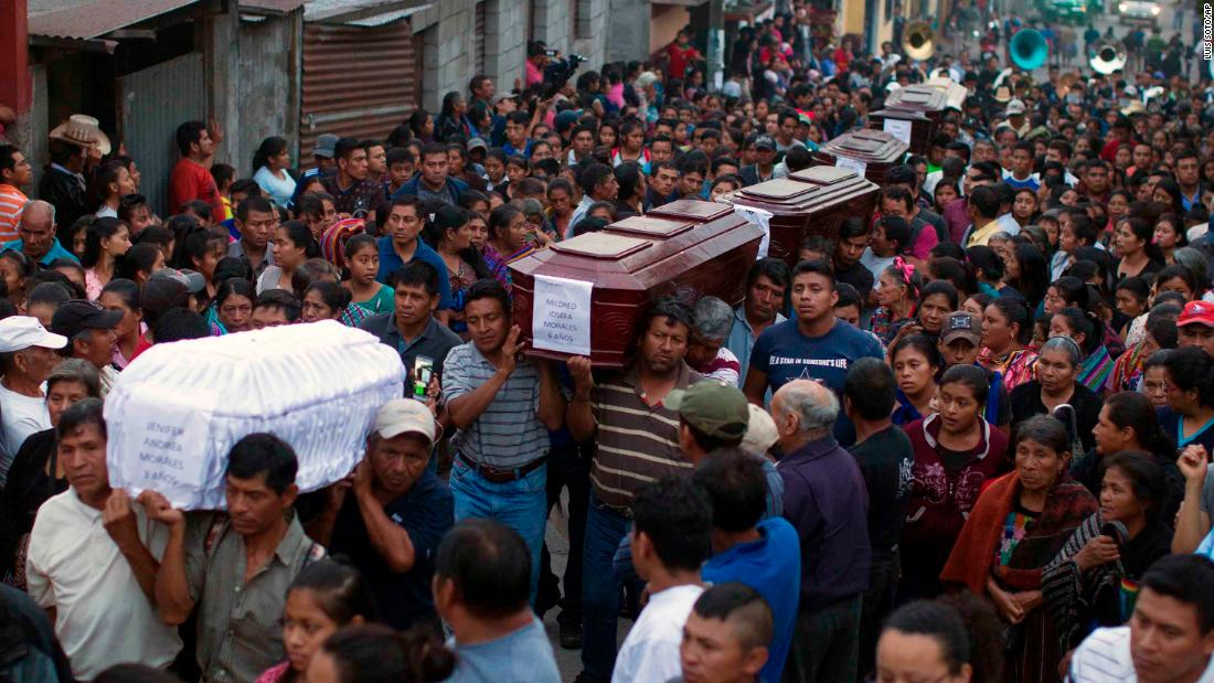 People carry the coffins of seven victims to the cemetery in Alotenango.