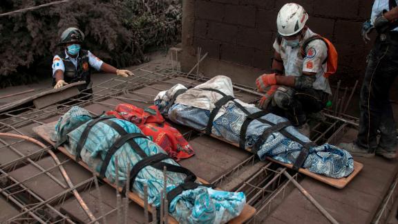 An emergency worker kneels beside bodies recovered in Escuintla on Monday, June 4.