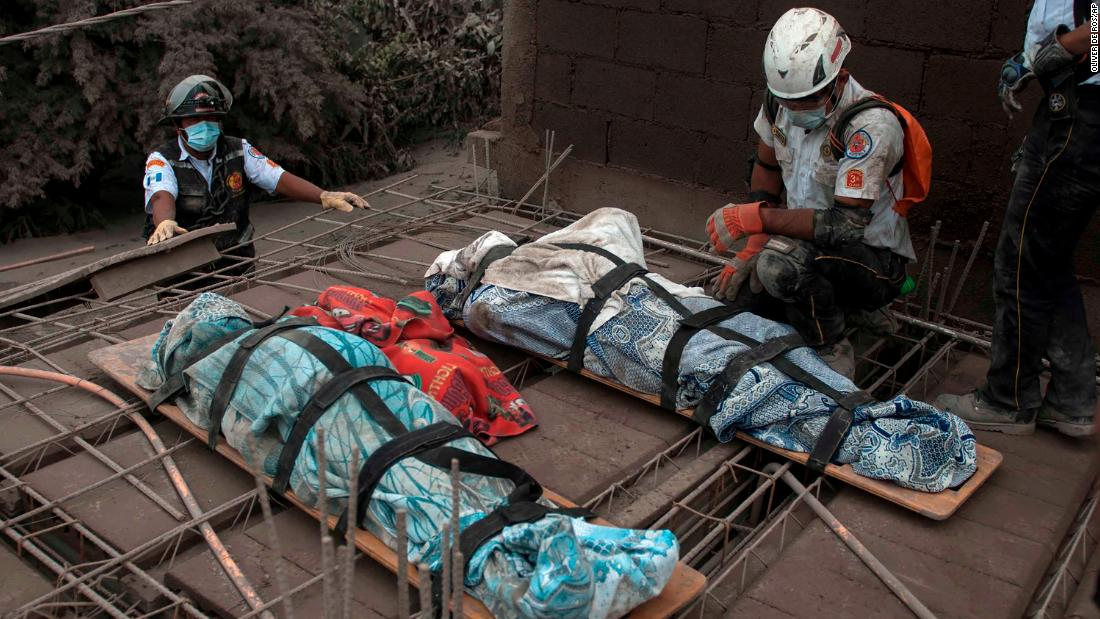 An emergency worker kneels beside bodies recovered in Escuintla on Monday, June 4.