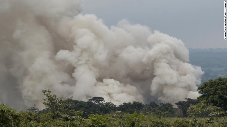 A smoke column forces rescuers Tuesday to evacuate the town of San Miguel Los Lotes.
