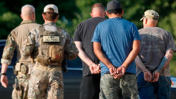 Government agents take suspects in custody during an immigration sting at Corso's Flower and Garden Center, Tuesday, June 5, 2018, in Castalia, Ohio. The operation is one of the largest against employers in recent years on allegations of violating immigration laws.  (AP Photo/John Minchillo)