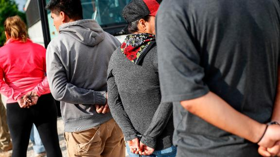 Suspects wait to be loaded onto a bus during an immigration sting at Corso's Flower and Garden Center, in Castalia, Ohio, earlier this month. (AP Photo/John Minchillo)