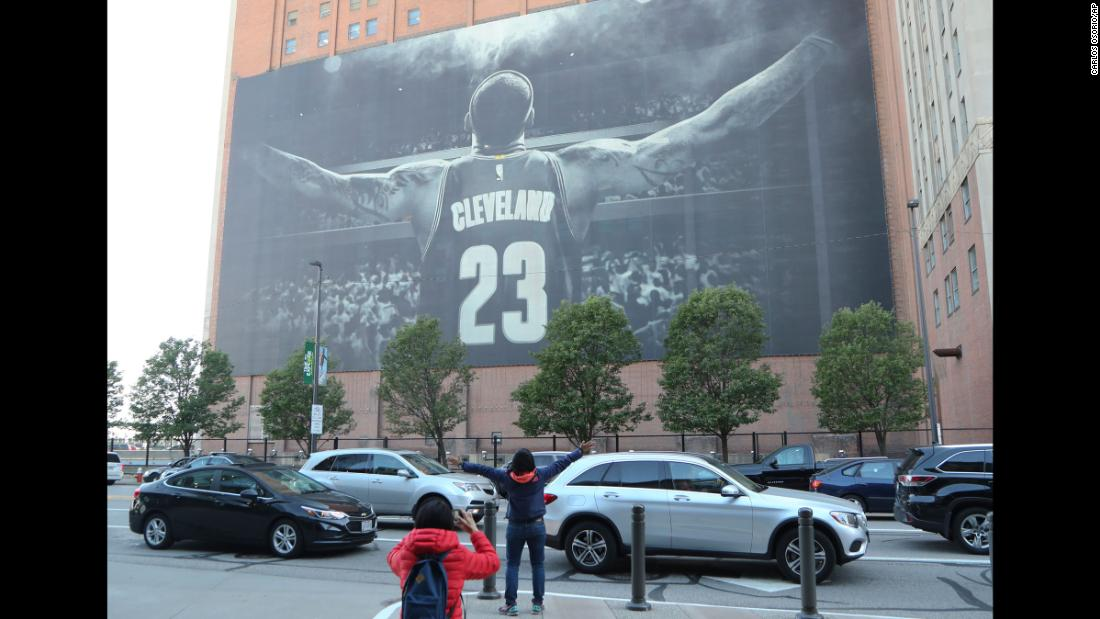 A fan poses in front of a LeBron James mural ahead of Game 3 in Cleveland.