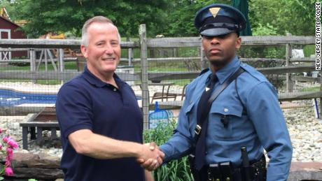 New Jersey State Trooper Michael Patterson, right, pulled over retired police officer Matthew Bailly and realized that Bailly had delivered him as a baby.