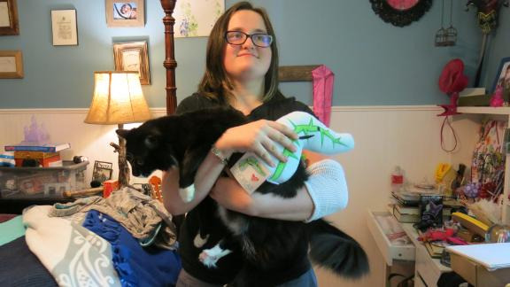Emmy Reeves holds her cat and a stuffed pancreas. She recently underwent a pancreas transplant that has transformed her life.