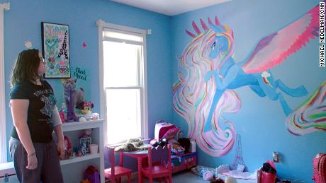 Emmy Reeves shows off the mural she painted in her sister's room after her transplant.