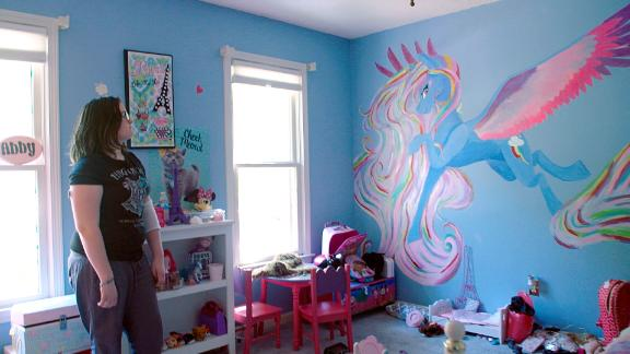 Emmy Reeves shows off the mural she painted in her sister