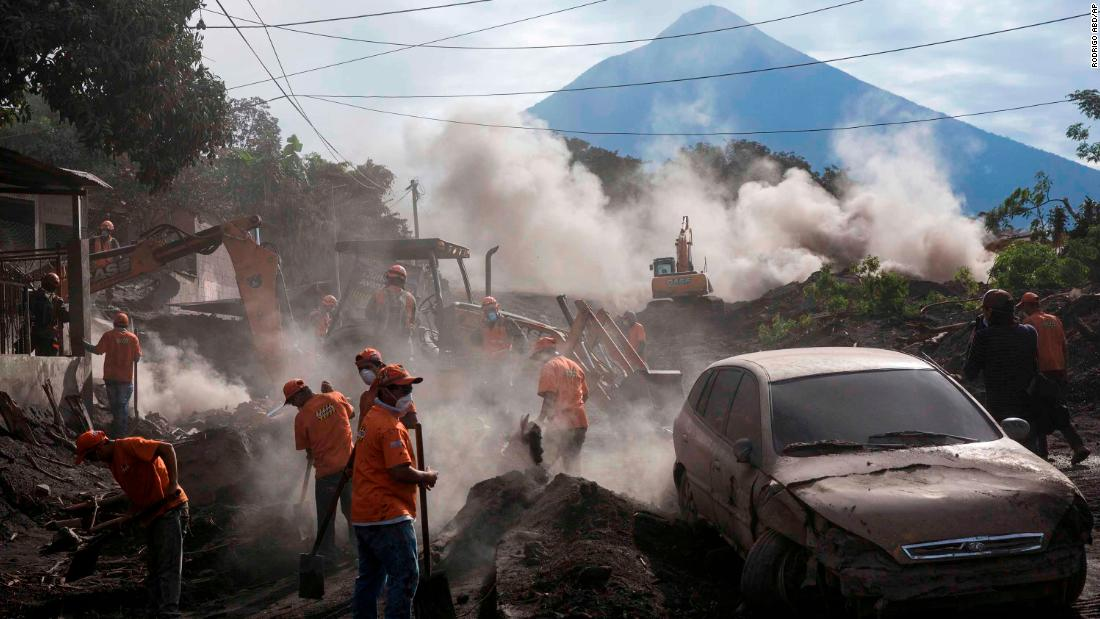 Days after the Fuego volcano erupted, rescue workers remove layers of ash in El Rodeo, Guatemala, on Wednesday, June 6.