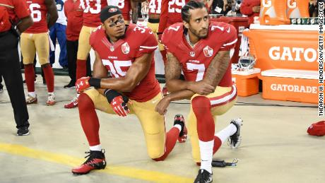 Colin Kaepernick #7 and Eric Reid #35 of the San Francisco 49ers kneel in protest on September 12, 2016 in Santa Clara, California.