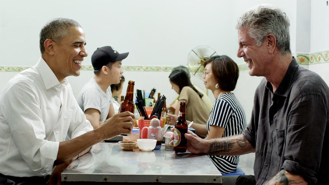 "Bourdain sits down with US President Barack Obama during a ""Parts Unknown"" episode in Hanoi, Vietnam, in 2016. Over a dish of bun cha, <a href=""https://www.cnn.com/travel/article/bourdain-parts-unknown-obama-hanoi/index.html"" target=""_blank"">Obama shared personal stories</a> and reflected on his own international travels."