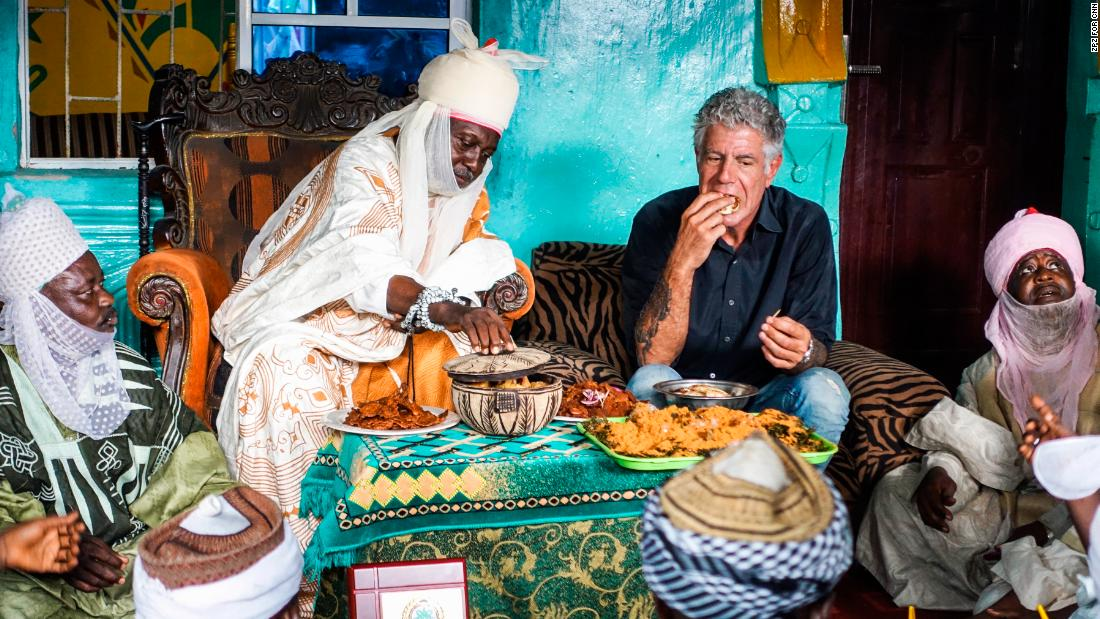 "Bourdain sits down for lunch with Hausa people in Lagos, Nigeria, in 2017. ""People open up to him and, in doing so, often reveal more about their hometowns or homelands than a traditional reporter could hope to document,"" said judges for the Peabody Award, who honored Bourdain in 2013."