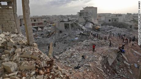 Syrians gather amid destruction in Zardana, Idlib province, in the aftermath of airstrikes Thursday.