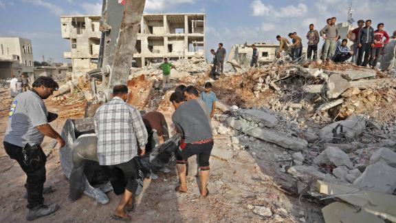 Syrian rescuers and civilians recover bodies in Zardana, in the mostly rebel-held northern Syrian Idlib province, in the aftermath of air strikes in the area, on June 8, 2018. - Air strikes in northwestern Syria, thought to have been carried out by regime ally Russia, killed 38 civilians including four children, a Britain-based monitor said. The raids, which hit a residential zone in the area of Zardana in the northwestern province of Idlib, also wounded 50 people, the Syrian Observatory for Human Rights monitoring group said. (Photo by OMAR HAJ KADOUR / AFP)        (Photo credit should read OMAR HAJ KADOUR/AFP/Getty Images)