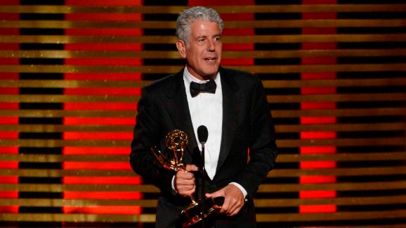 "Bourdain accepts an Emmy Award for ""Parts Unknown"" in 2014."