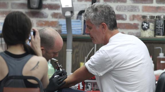 Bourdain and his second wife, Ottavia, get matching snake tattoos in South Beach, Florida, in 2011. The two divorced in 2016.