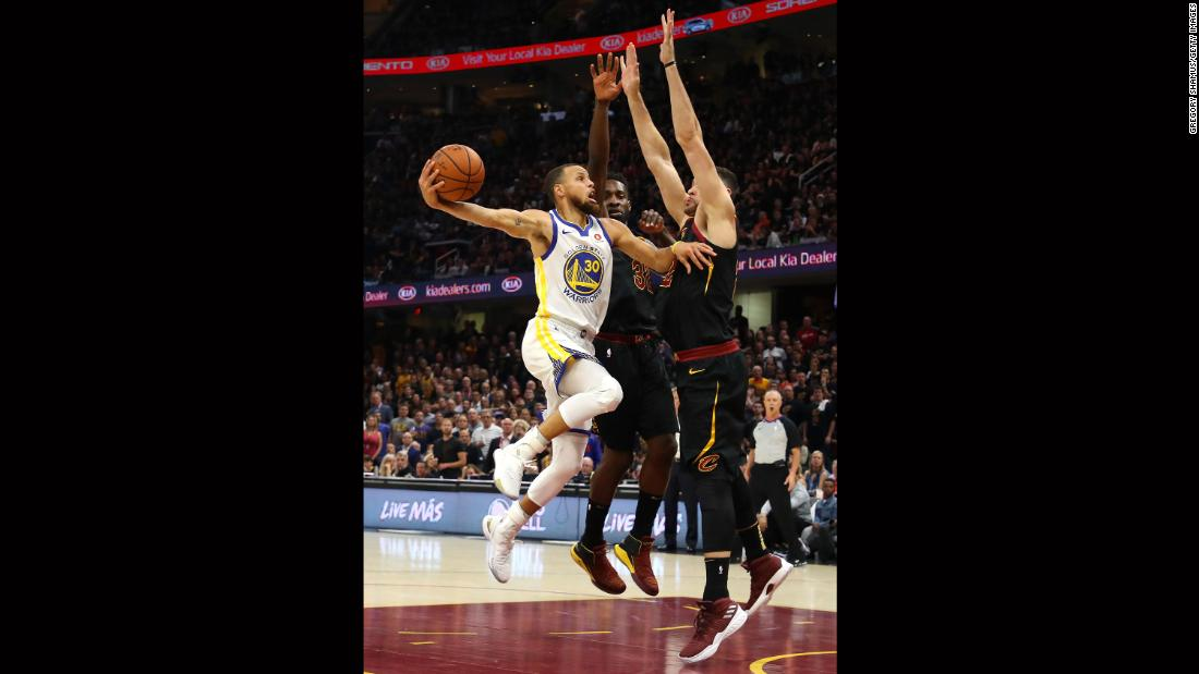 Curry tries to shoot over two Cleveland defenders in the first half of Game 4. Curry had 20 points for the Warriors in the first half, and he finished with a game-high 37.