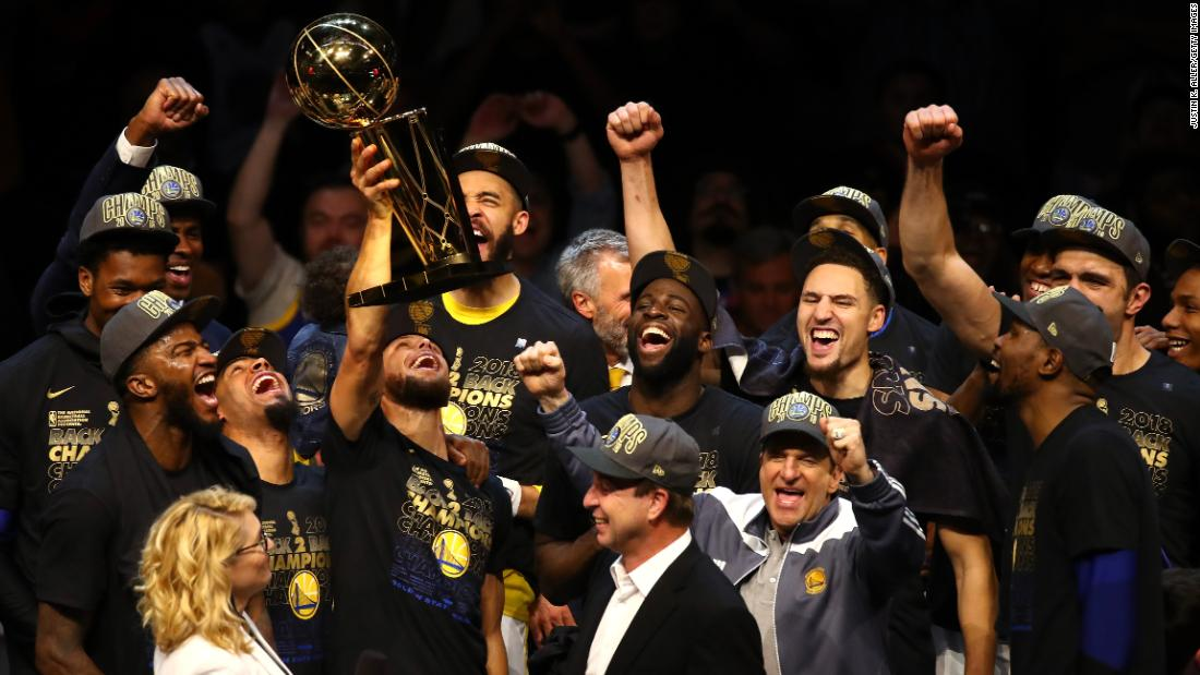 The Golden State Warriors celebrate with the Larry O'Brien Trophy after winning Game 4 of the NBA Finals on Friday, June 8. The Warriors defeated Cleveland 108-85 to complete a series sweep and claim their third title in four years.
