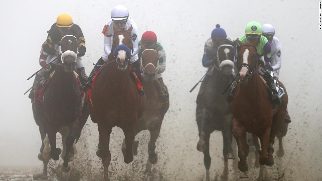 Justify (No. 7), ridden by jockey Mike Smith, leads the field into the first turn during the 143rd running of the Preakness Stakes at Pimlico Race Course on May 19, 2018, in Baltimore.