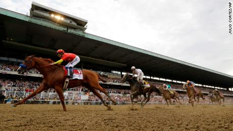 Justify (1), with jockey Mike Smith up, crosses the finish line to win the 150th running of the Belmont Stakes horse race and the Triple Crown, Saturday, June 9, 2018, in Elmont, N.Y. (AP Photo/Julio Cortez)