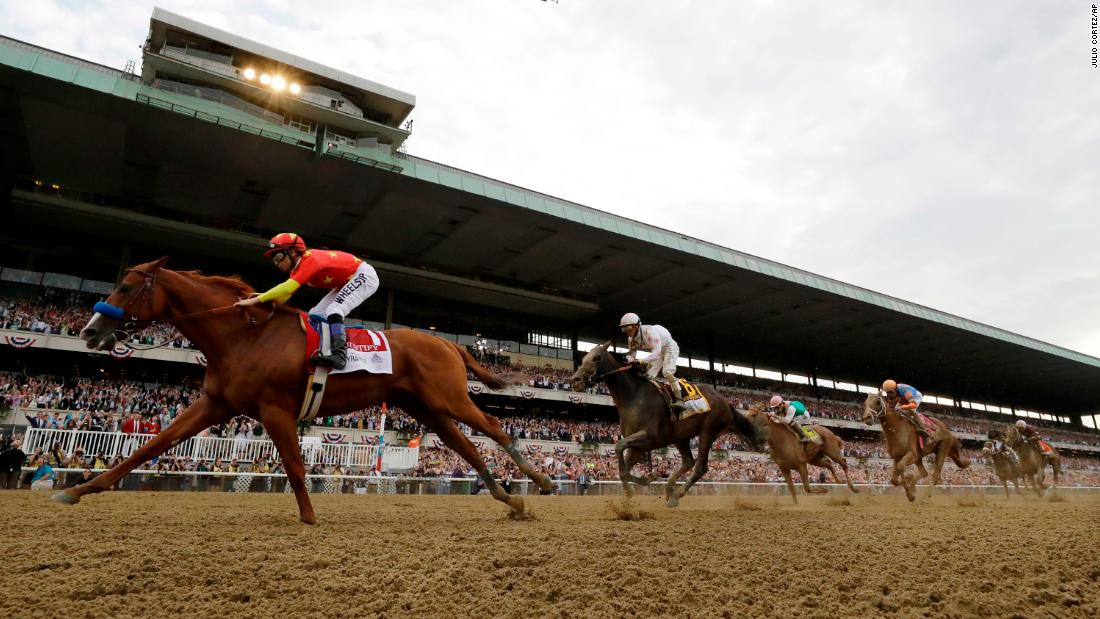 Justify, left, with jockey Mike Smith, crosses the finish line to win the 150th running of the Belmont Stakes horse race on Saturday, June 9, 2018, in Elmont, New York. Justify became the 13th thoroughbred to win horse racing's Triple Crown, taking first in the Kentucky Derby and Preakness Stakes last month.