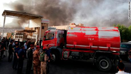 Iraqi security forces and firefighters gather as smoke rises from the blaze.