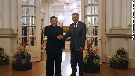 "North Korea's leader Kim Jong Un (L) is welcomed by Singapore's Prime Minister Lee Hsien Loong (R) during his visit to The Istana, the official residence of the prime minister, following Kim's arrival in Singapore on June 10, 2018. - Kim Jong Un and Donald Trump will meet on June 12 for an unprecedented summit in an attempt to address the last festering legacy of the Cold War, with the US president calling it a ""one time shot"" at peace. (Photo by ROSLAN RAHMAN / AFP)"