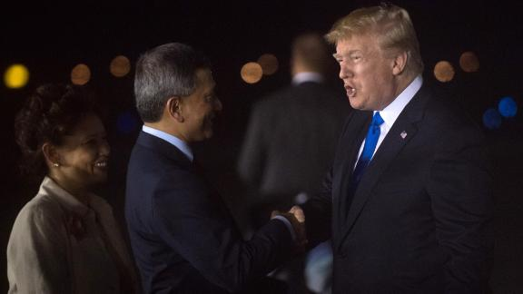 US President Donald Trump (R) is welcomed by Singapore