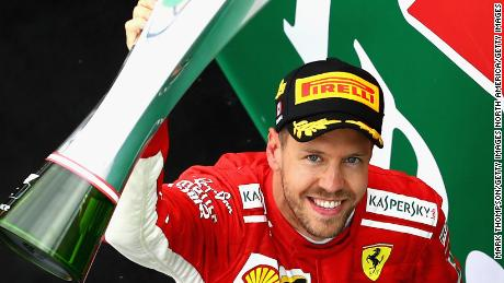 Race winner Sebastian Vettel of Germany and Ferrari celebrates on the podium after his Canadian Grand Prix victory.
