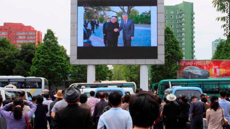 People watch a large screen at the main train station airing video of North Korean leader Kim Jong Un shaking hands with Singapore Prime Minister Lee Hsien Loong during his trip to Singapore in Pyongyang, North Korea, on Monday. Kim is in Singapore to attend a summit with US President Donald Trump.