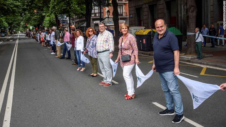 Basque Nationalist Party's senior officials Andoni Ortuzar (right to left) and Itxaso Atutxa and Bilbao Mayor Juan Mari Aburto take part in the human chain in Bilbao, northern Spain.