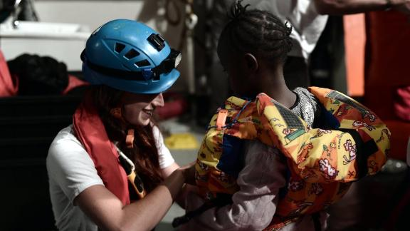 A rescue worker helps a young child on board the Aquarius.