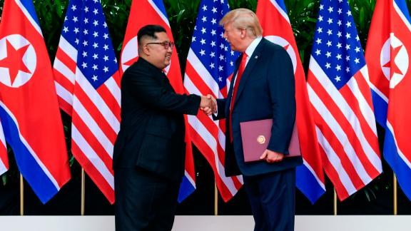 North Korea leader Kim Jong Un (L) and US President Donald Trump shake hands after their meetings at the Capella resort on Sentosa Island in Singapore on June 12, 2018.