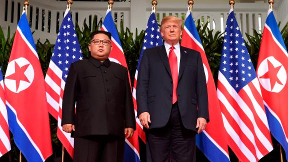 TOPSHOT - US President Donald Trump (R) poses with North Korea