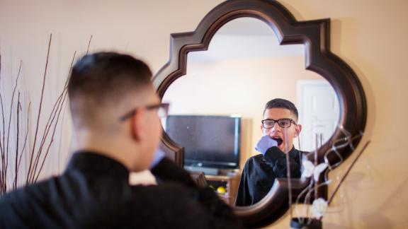 New Jersey. Kevin Portillo does one of his exercises before church on Sunday morning, massaging his cheek with a gloved hand. Kevin was born with a rare tumour covering half of his face which had to be removed. Despite an initially grim prognosis, he has grown into a churchgoing 13-year-old who loves soccer and video games. Now, with the help of surgery and physical therapy, he is perfecting his smile.