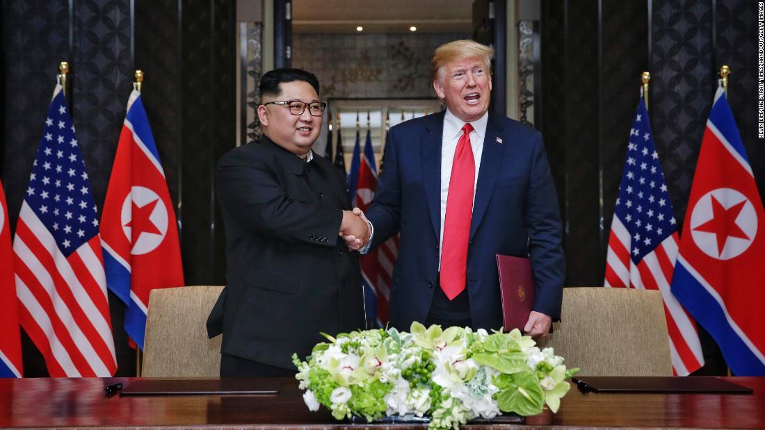In this handout photograph provided by The Strait Times, North Korean leader Kim Jong-un (L) with U.S. President Donald Trump (R) during their historic U.S.-DPRK summit at the Capella Hotel on Sentosa island on June 12, 2018 in Singapore.  (Photo by Kevin Lim/The Strait Times/Handout/Getty Images)