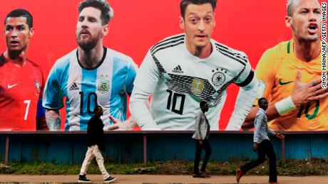 People walk past a football billboard displaying    Portugal's forward Cristiano Ronaldo, Argentina's forward Lionel Messi, Germany's midfielder Mesut Ozil and Brazil's striker Neymar in Nairobi, ahead of the Russia 2018 World Cup.