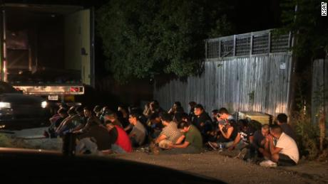 Undocumented immigrants found in an 18-wheeler truck sit while being detained by authorities.