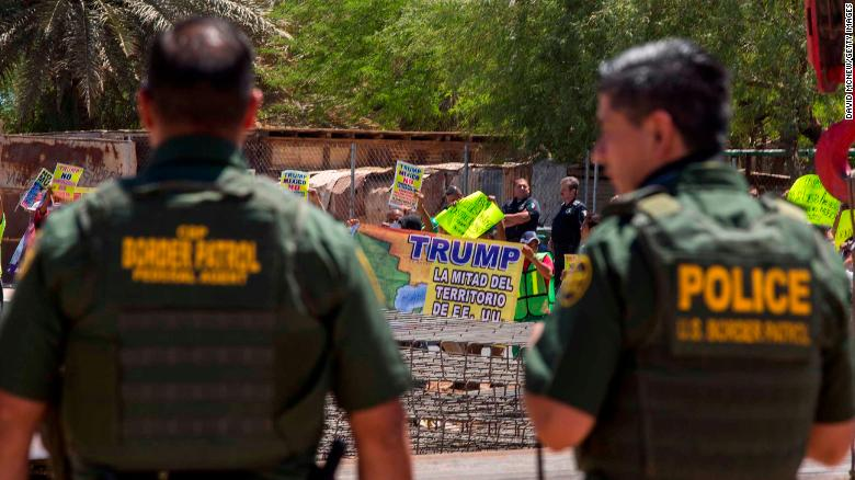 CALEXICO, CA - APRIL 18: Border agents watch as protesters on the Mexico side of the border demonstrate against policies of President Donald Trump while U.S. Department of Homeland Security Secretary Kirstjen Nielsen tours a replacement border fence construction site on April 18, 2018 in Calexico, California. President Trump recently bashed  California Gov. Jerry Brown after a decision to limit the mission of California National Guard troops at the Mexico border.  (Photo by David McNew/Getty Images)