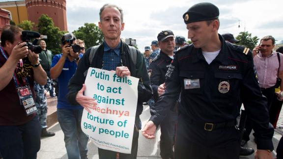 "Russian police detane Gay rights activist Peter Tatchell, center, as he holds a banner that read ""Putin fails to act against Chechnya torture of gay people"" near Red Square in Moscow, Russia, Thursday, June 14, 2018. A British LGBT activist has been detained has been detained near the Red Square for holding a one-man protest against Russia"