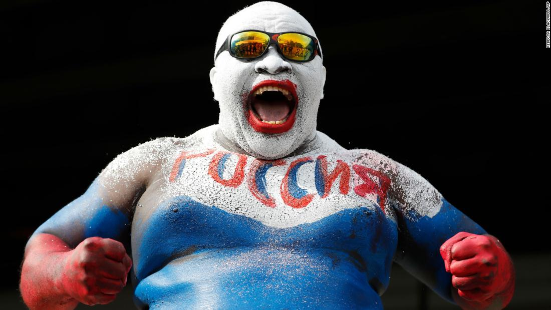 A fan wears body paint in Russia's colors before the opening match.