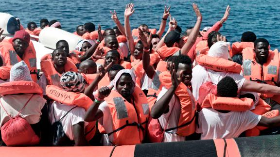 Migrants wave after being transferred from the Aquarius ship to Italian Coast Guard boats on June 13, 2018 in the Mediterranean Sea.