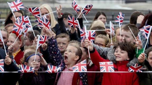 Schoolchildren near Runcorn Station wait to see the monarch and new royal arrive in the Cheshire town to open a new toll bridge nearby.
