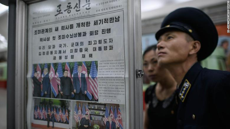 A conductor reads the latest edition of the Rodong Sinmun newspaper showing images of North Korean leader Kim Jong Un meeting with US president Donald Trump during their summit in Singapore, at a news stand on a subway platform of the Pyongyang metro on June 13, 2018.