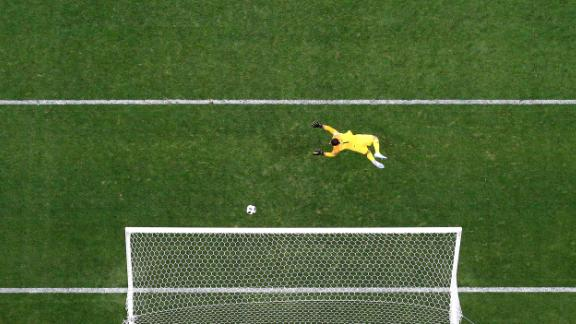 The ball flies past Saudi Arabian goalkeeper Abdullah Al-Mayouf for Russia