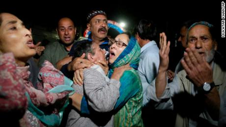 Relatives and friends of journalist Shujaat Bukhari cry inside a police control room in Srinagar, India, Thursday, June 14, 2018.  Mukhtar Khan/AP