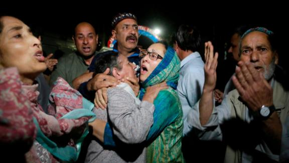 Relatives and friends of journalist Shujaat Bukhari cry inside a police control room in Srinagar, India, Thursday, June 14, 2018.  Mukhtar Khan/AP